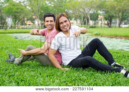 Portrait Of Two Smiling Handsome Young Men Pointing At Viewer And Sitting On Grass In Park. Motivati