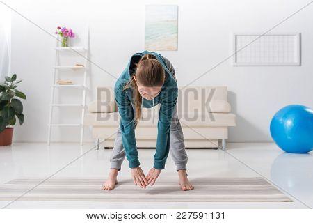 Girl Exercising On Yoga Mat At Home