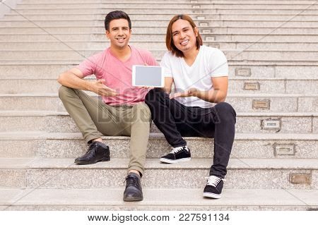 Portrait Of Two Smiling Handsome Young Men Looking At Camera And Showing Blank Tablet Computer Scree