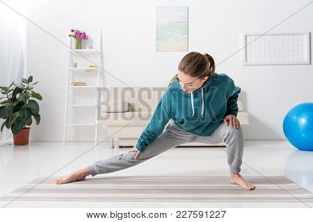 Girl Stretching Legs On Yoga Mat At Home