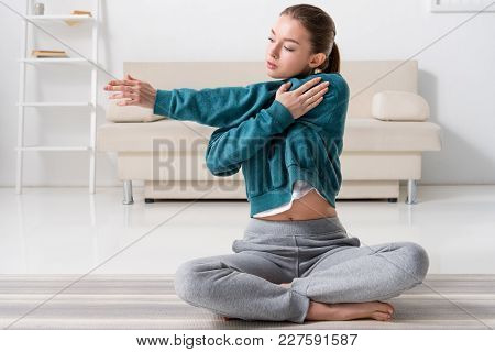 Girl Sitting In Lotus Position On Yoga Mat And Stretching Hands At Home