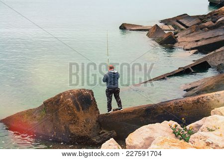 Man Catches Fish While Standing On The Huge Stones