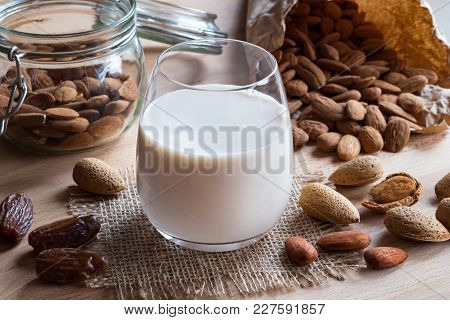 A Glass Of Almond Milk On A Wooden Table With Almonds And Dates