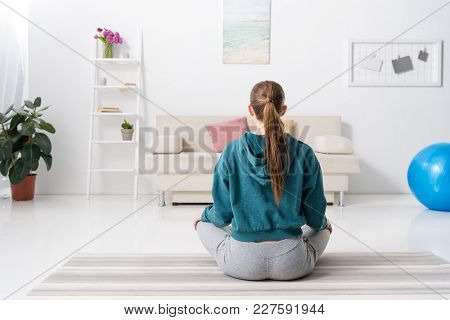 Rear View Of Girl Sitting In Lotus Position On Yoga Mat At Home