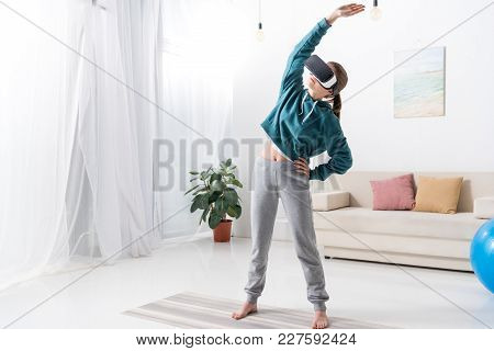 Girl Standing And Stretching With Virtual Reality Headset On Yoga Mat At Home
