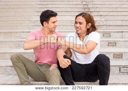 Closeup Portrait Of Two Smiling Handsome Young Men Fist Bumping On Outdoor Stairway. Men Friendship