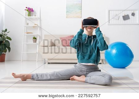 Sportive Girl Stretching With Virtual Reality Headset On Yoga Mat At Home
