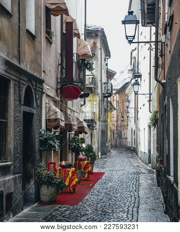 Quaint Cobblestone Alleyway In Aosta, Italy With Inviting Red Carpet Entrance To Italian Restaurant