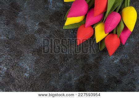 Handmade tulips on darken concrete background for Mother's Day, spring time or Easter theme.