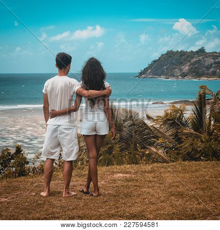 Romantic young couple on a tropical island paradise standing arm in arm looking out over a tranquil blue ocean and palm trees