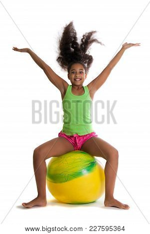 A Beautiful Dark-skinned Girl Jumps On A Yellow Ball. The Girl Is Raised Up.