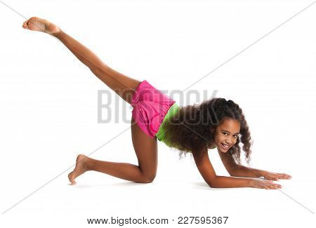 A Little Dark-skinned Girl Gymnast Performs Exercises.