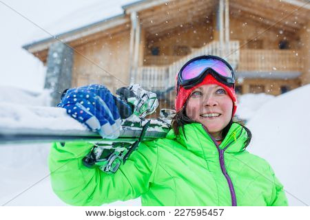 Smiling brunette in helmet with skis on shoulder against background of wooden building