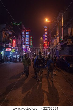 The Group Of Foreign Tourists In Poor Criminal Blighted Area Along Main Bazar Street, Delhi, India.