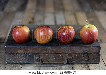 Big Red Apples In A Dark Wooden Box. Wooden Crate And Apples On A Wooden Table In The Kitchen.