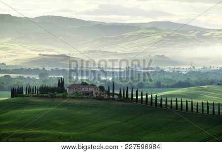 Tuscany countryside panorama, green field and farm house, Italy