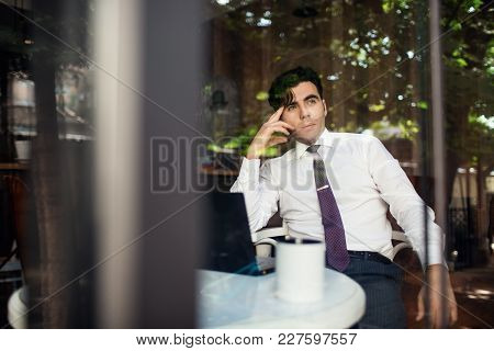 Handsome Elegant Businessman Sitting At Reastaurant And Reading On Tablet.