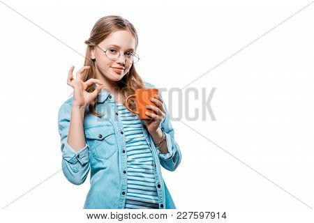 Beautiful Girl In Eyeglasses Holding Mug Of Tea And Showing Ok Sign Isolated On White