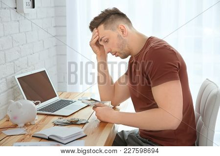 Stressed man counting money at table indoors