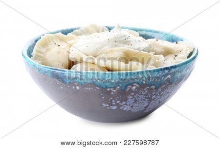 Tasty dumplings with sour cream in bowl on white background