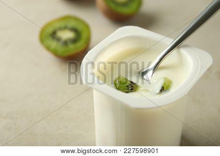 Plastic cup with yummy kiwi yogurt and spoon on table, closeup