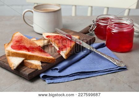 Delicious toasts with sweet jam on wooden board