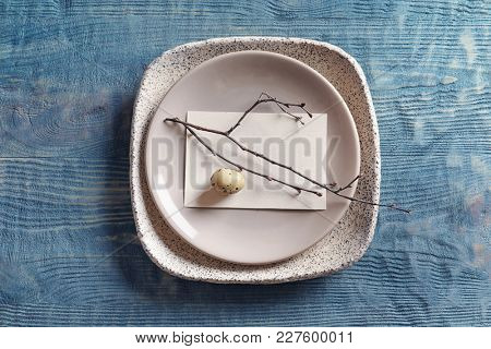 Beautiful festive Easter table setting with blank card on wooden background