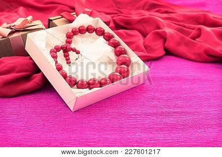 Bright Necklace Is Packed In A White Box On A Pink Background. A Gift To A Woman For The Holiday. Th