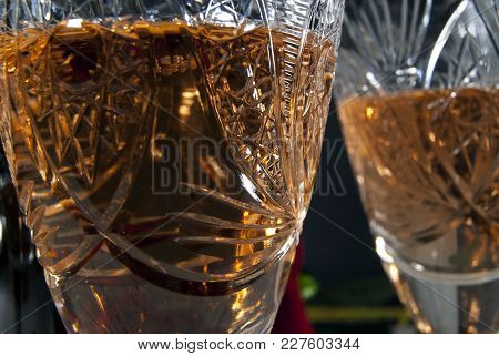 Vintage Faceted Crystal Glasses With White Wine Close-up On A Dark Background, Focus On The Surface