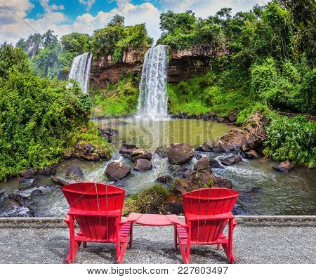 Scenic basaltic rock form famous waterfalls Iguazu Falls. Two large red plastic chairs - chaise lounges set at waterfalls. The concept of ecological tourism