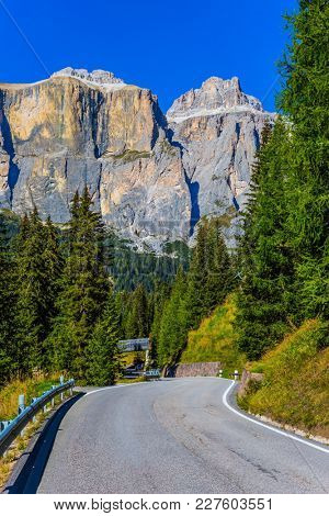 Majestic white mountains and rocks. The road passes in the limestone and dolomite rocks. Dolomite Alps. The concept of active, extreme and automobile tourism