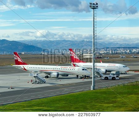 Tbilisi, Georgia, 12/07/2017: Two Georgian Airplanes Airzena Airways Are Parked At Airport. In Backg