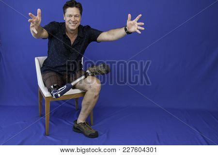 Middle-aged Man With Physical Disability, Happy With Life Sitting On The Chair