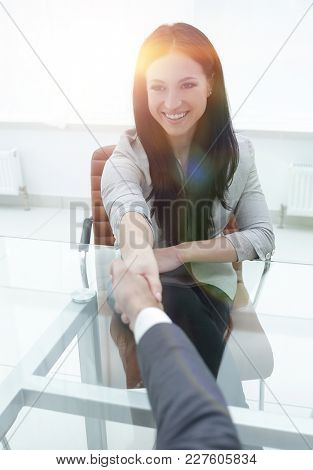 handshake young business woman with a partner in the office