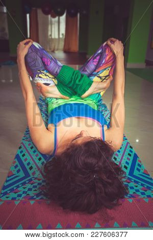 young woman lying on mat with legs in lotus position indoor shot from above view