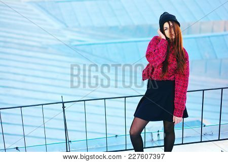 Portrait Of A Cute Young Woman In A Plaid Shirt And Short Skirt With Frayed Wind Hair Standing Near