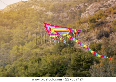 Beautiful, Bright, Striped, Airy Kite Flies In The Sky Over The Mountains