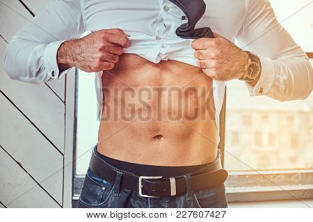 Portrait Of Stylish Muscular Man Shows His Abdominal Muscles, Raising His Shirt With His Hand.