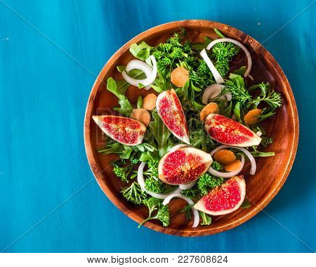 Autumn Salad Of Arugula, Figs In Brown Earthenware Plate On A Blue Background. Top View