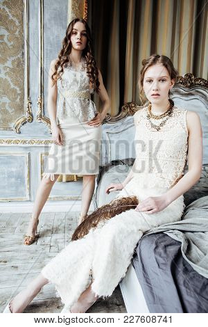 Two Pretty Twin Sister Blond Curly Hairstyle Girl In Luxury House Interior Together, Rich Young Peop
