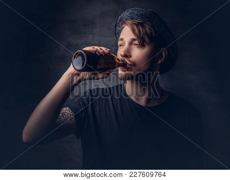 Portrait Of An Attractive Hipster Male With Tattooed Arms, Dressed In A Black T-shirt And Hat Drinks