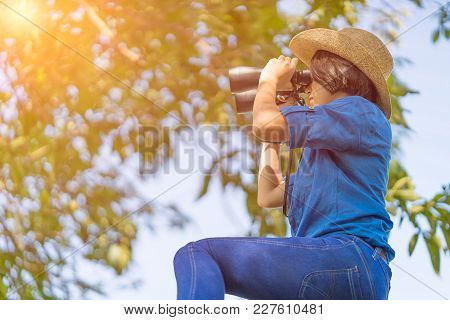 Close Up Woman Wear Hat And Hold Binocular In Grass Field