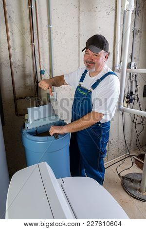 Hopeless Home Installer Having Trouble Installing A New Household Water Softener Giving A Thumbs Dow