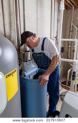 Workman Replacing An Old Domestic Water Softener Looking Into Problems Encountered When Installing T