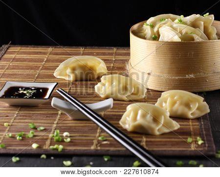 Japanese Gyoza.dumplings In Bamboo Steamer. Sticks And Soy Sauce