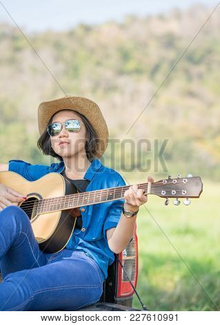Young Asian Women Short Hair Wear Hat  Playing Guitar ,sit On Pickup Truck In Countryside Thailand