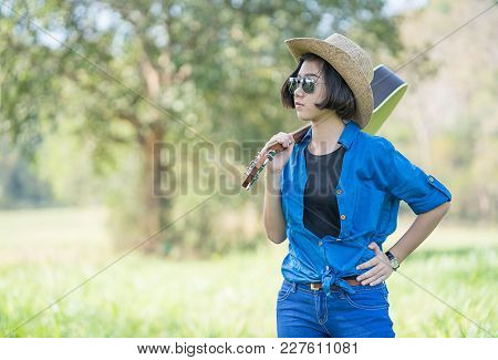 Woman Wear Hat And Carry Her Guitar In Grass Field
