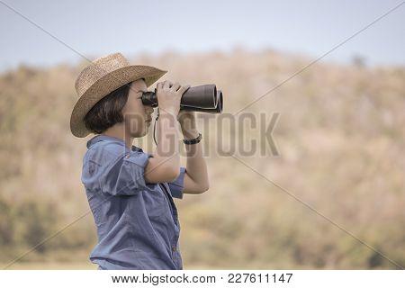 Woman Wear Hat And Hold Binocular In Grass Field