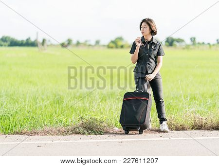 Young Asian Woman Short Hair And Wearing Sunglasses Sit With Backpack Hitchhiking Along A Road Wait