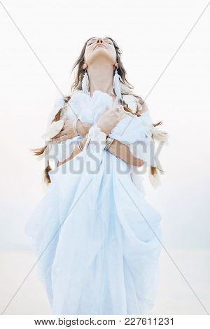 Beautiful Young Boho Woman In White Dress And Feathers Posing On The Beach. Bridal Concept